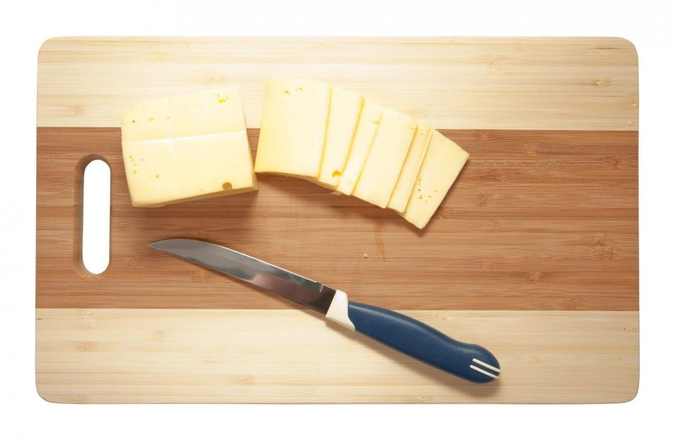 Chef's knife hopping an cheese on an wooden cutting board - white background